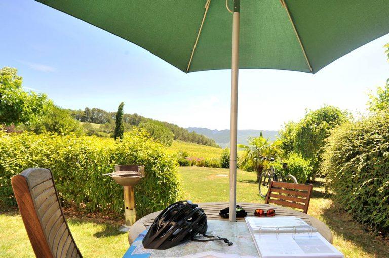 Photographie d'un jardin avec un vélo, un casque et une carte IGN