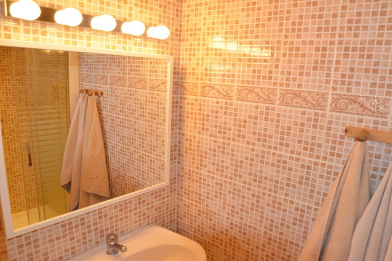 Photographie d'une salle de bains avec un lavabo et une douche