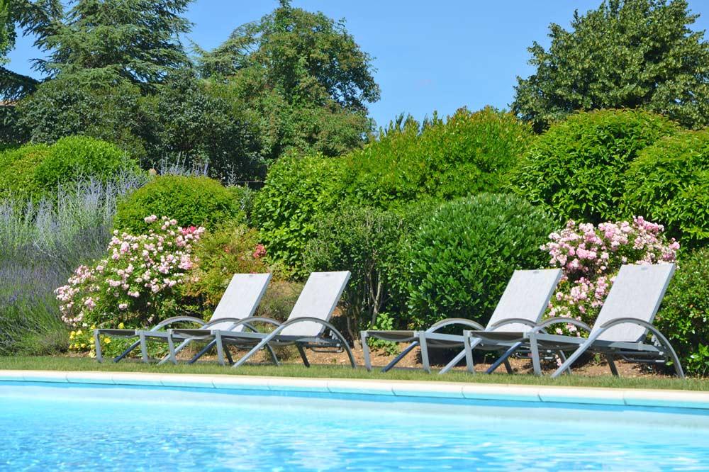 Photographie d'un jardin fleuri avec une piscine