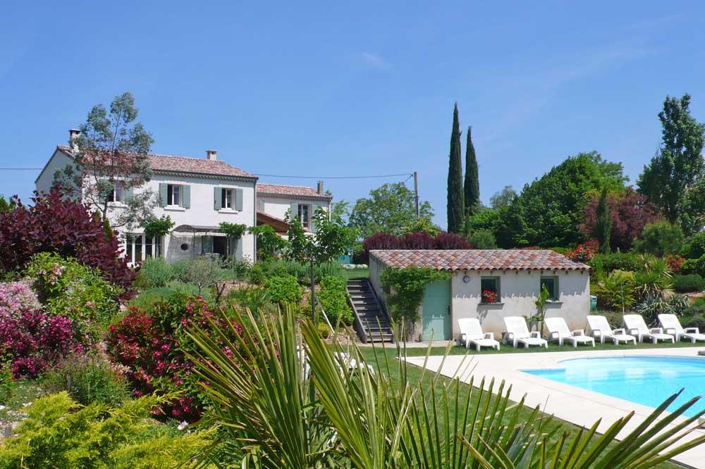 Photographie d'un piscine et d'un jardin avec un palmier